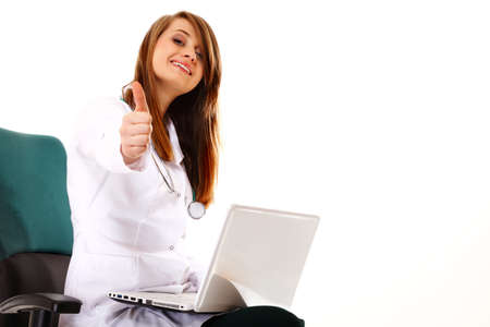 Female doctor working on her laptop showing thumbs up against a white background photo