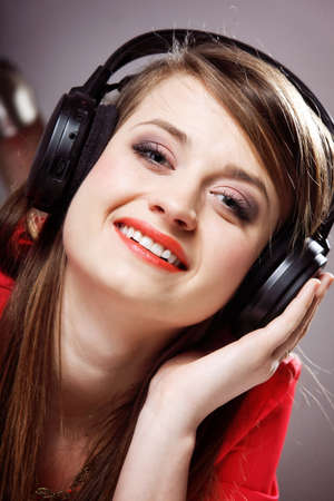 Close up smiling girl with headphones listen music on the grey background photo