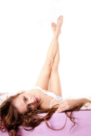 head tilted: A beautiful happy woman lying on her back in bed with head tilted to the camera and her feet crossed in the air