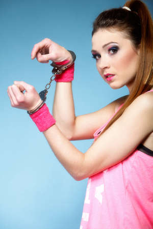 handcuffed: teen crime - teenager girl in handcuffs studio shot blue background Stock Photo