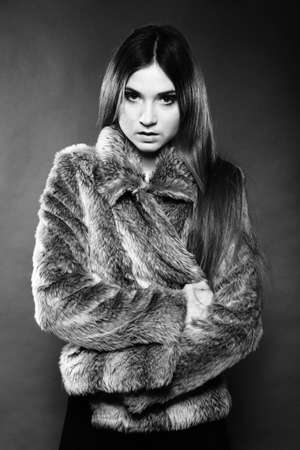 portrait of fashionable woman in fur coat dark background, monochrome shot photo