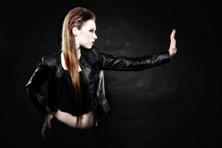 Subculture beauty punk girl in leather jacket making stop gesture black background photo