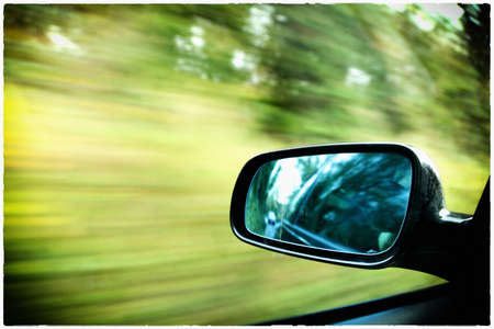 car on the road wiht motion blur background and rear view mirror photo