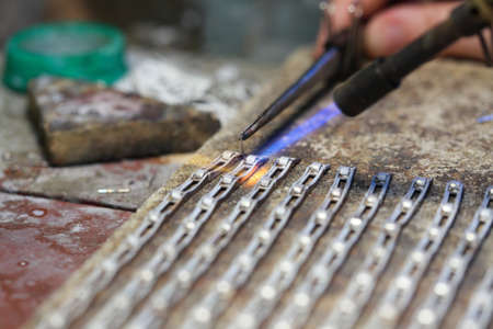 hands of jeweller at work silver soldering. Goldsmith working and welding.