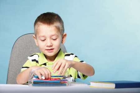 little boy drawing with color pencils on blue background Stock Photo - 18551325