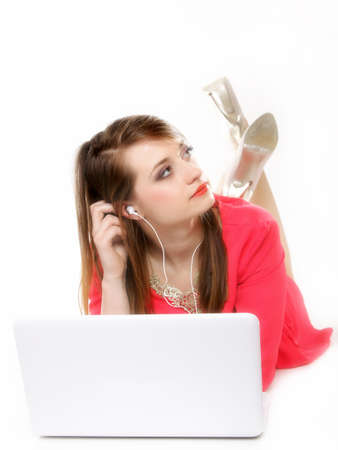 cute girl with headphones listening to music on the laptop on white background photo