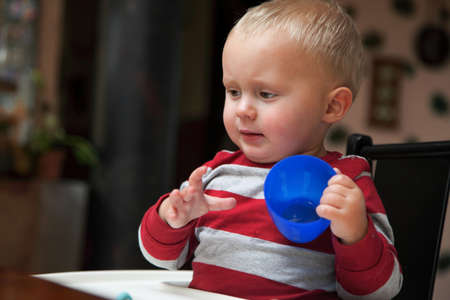 baby boy playing with bottle and mug drinking indoor Stock Photo - 18567778