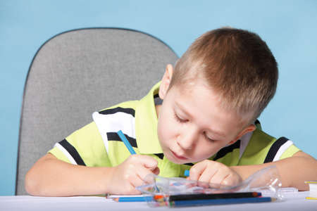 little boy drawing with color pencils on blue background Stock Photo - 18567897