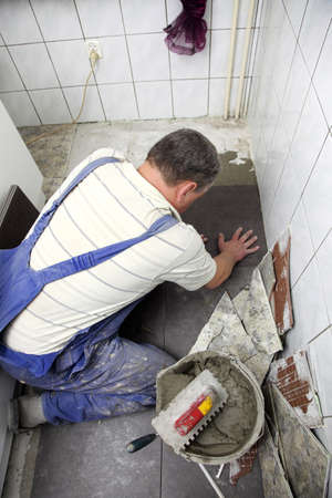 a tiler at work. bonding of floor tile with tile adhesive and filler. photo