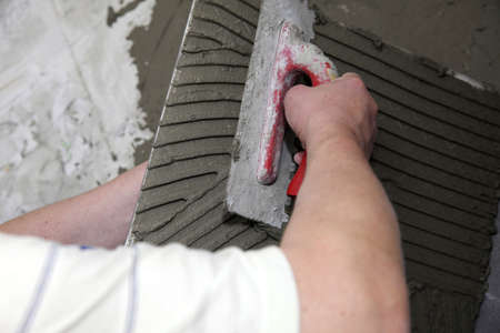 a tiler at work. bonding of floor tile with tile adhesive and filler. Stock Photo - 18593447