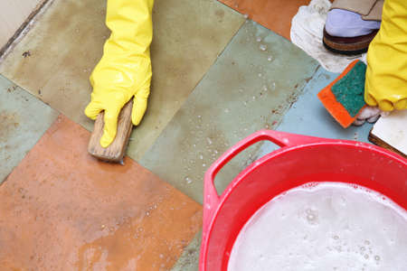 Hand in yellow glove cleaning dirty filthy floor with brush indoors photo