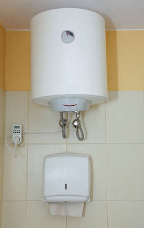 Paper towel dispenser and electric water heater on the wall in the bathroom photo