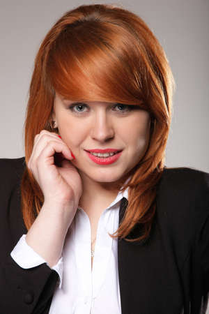 closeup picture of a beautiful redhaired business womans face, grey background photo