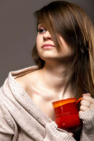 Closeup of a beautiful thoughtful sad woman holding a nice red cup of warm beverage gray background photo