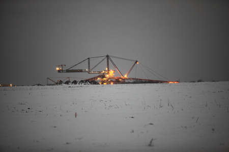 Bucket wheel excavator digging for brown coal winter night view Poland. Extractive industry photo