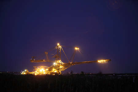 bucket wheel excavator digging for brown coal night view Poland extractive industry photo