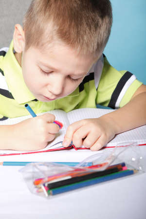 little boy drawing with color pencils on blue background Stock Photo - 18627543