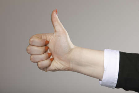 Female hand  thumb up gesturing the all right symbol , ok sign gray background photo