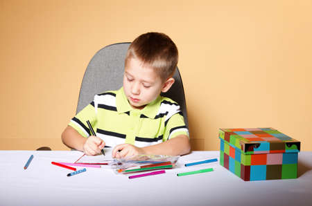 little boy drawing with color pencils on orange background Stock Photo - 18661968