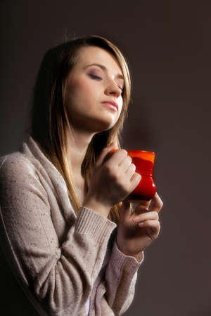 Closeup of a beautiful caucasian woman holding a nice red cup of warm beverage gray background Stock Photo - 18686964