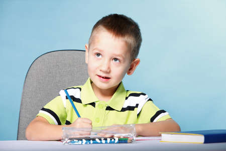 little boy drawing with color pencils on blue background Stock Photo - 18758334