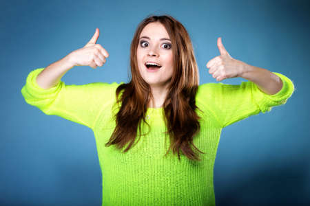 Happy smiling woman in bright vivid colour sweater with thumbs up gesture, on blue background photo