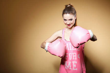 Female boxer model wearing big fun pink gloves playing sports boxing studio shot, brown background photo