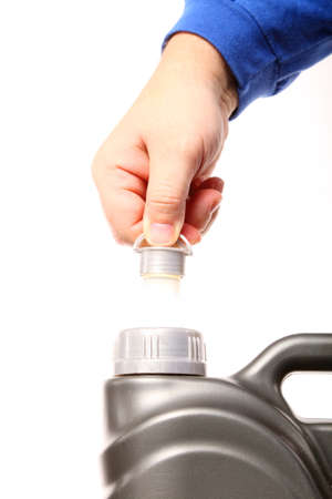 Closeup hand opening canister with car engine oil white background photo