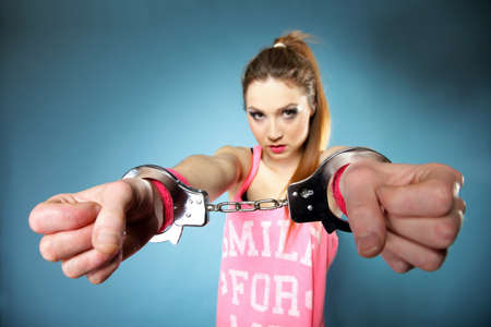 cuffed: teen crime - teenager girl in handcuffs studio shot blue background Stock Photo