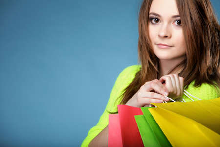 young woman in bright vivid colour sweater with paper multi coloured shopping bags on blue background