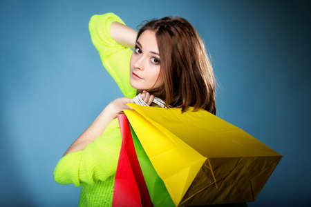 young woman in bright vivid colour sweater with paper multi coloured shopping bags on blue background. Sales and discounts concept. Stock Photo - 18810063