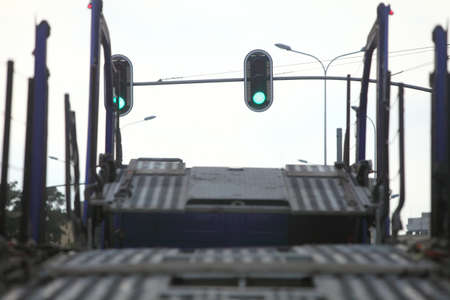 car carrier: Closeup empty car carrier truck on road. Traffic lights in city.