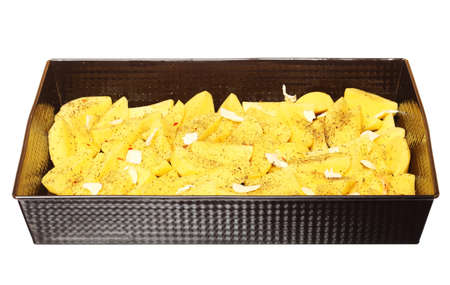 Raw peeled potatoes in tray with spices, butter slices ready to be roasted white background photo
