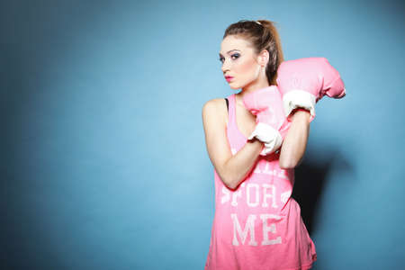 Female boxer model wearing big fun pink gloves playing sports boxing studio shot, blue background photo