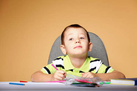 little boy drawing with color pencils on orange background Stock Photo - 18906088