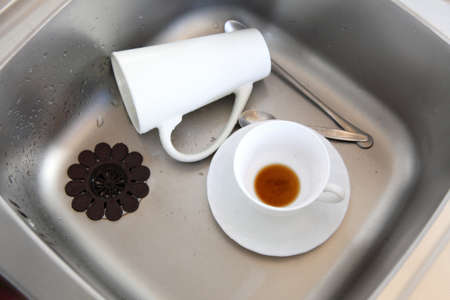 vessel sink: Washing up. White coffee cups in the kitchen sink.