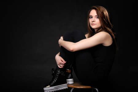 Girl with casual shoes. Women loves shoes concept. Black background photo
