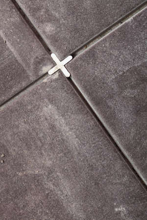 lying on the floor: Tiling preparation Spacer and prepared setting compound for tile lying Floor tiles
