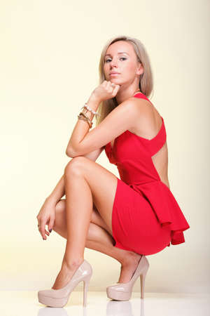 full lenght Portrait of pretty young woman in red dress against yellow background photo