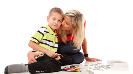 mother playing puzzle together with her son on floor isolated on white background photo