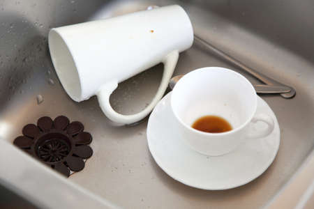 Washing up. White coffee cups in the kitchen sink. photo
