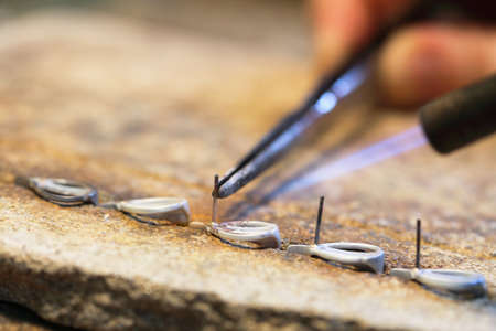 creative artist: hands of jeweller at work silver soldering. Goldsmith working and welding.