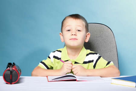 little boy drawing with color pencils on blue background Stock Photo - 18987916