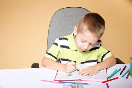 little boy drawing with color pencils on orange background Stock Photo - 18987948