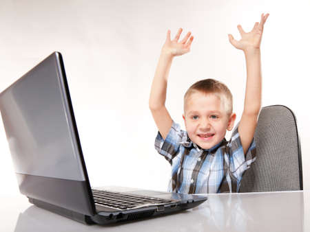 Triumphing child boy with a laptop notebook computer isolated on white background. Computer addiction. photo