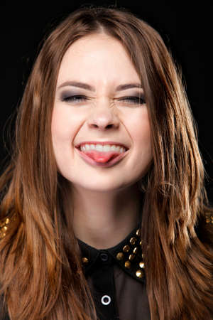 Grimacing young woman making silly face sticking out her tongue on black background photo