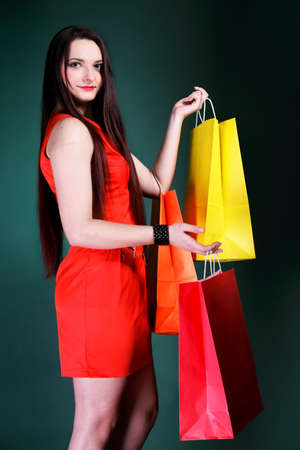 mmc: young woman long hair with paper multi coloured shopping bags on green background  Sales and discounts concept