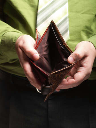 Poor economy represented by empty wallet in businessmans hands photo