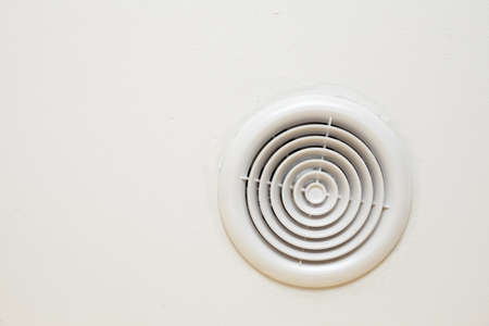 circular plastic air vent in white wall ventilation grille Stock Photo