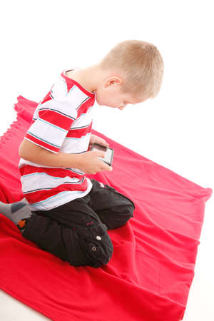 Little boy playing games on smartphone or reading a text message isolated on white background photo